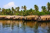 Photo of many boathouses in a row at the Kerala Backwaters, near Kochi, Kerala state, India.