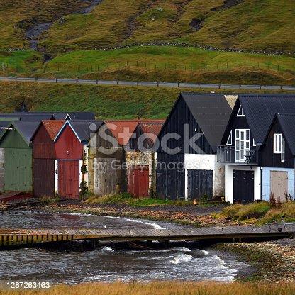 Colourfull boathouses on the shoreline of the small village of Hvalvik on Faroe Islands
