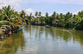 Boathouses and canoes sailing in the backwaters in Alappuzha, which is also known as Alleppey, Kerala, India.