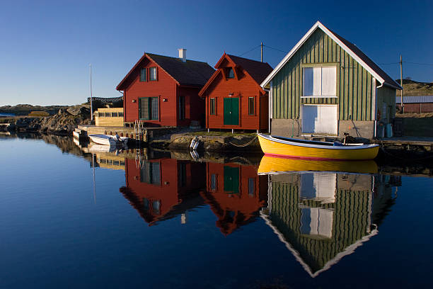 Boathouses with reflection, Kvtsoey Island, Norway. stock photo