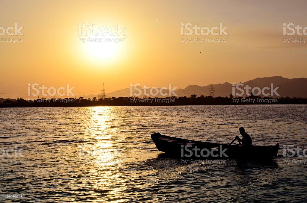 Boating at lake during sunset stock photo