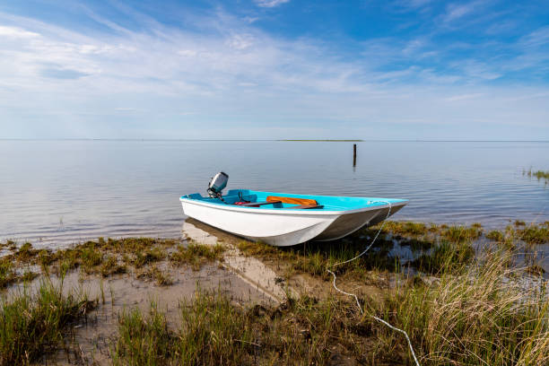 Boating on Ocracoke Island A beached skiff in the marshes on Ocracoke island, North Carolina. sailing dinghy stock pictures, royalty-free photos & images