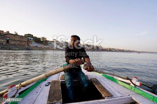 Varanasi, Uttar Pradesh, India - 24 March 2019: Boatman riding boat at river Ganga