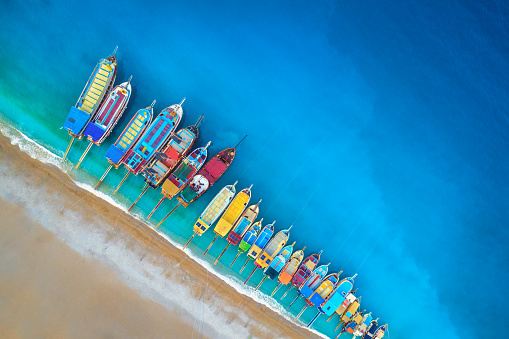 Boats. Aerial view of colorful boats in mediterranean sea in Oludeniz, Turkey. Beautiful summer seascape with ships, clear azure water and sandy beach at sunrise. Top view of yachts from flying drone