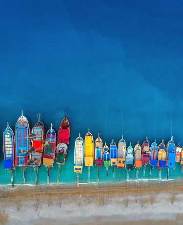 istock Boats. Aerial view of colorful boats in mediterranean sea in Oludeniz, Turkey. Beautiful summer seascape with ships, clear azure water and sandy beach in sunny day.Top view of yachts from flying drone 831502400