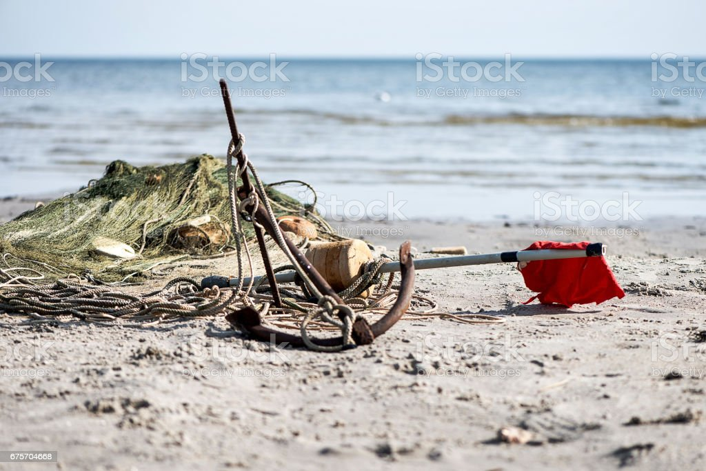 Boats anchor and fishing nets in the beach sand. royalty-free stock photo