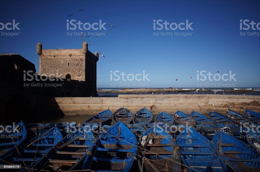 boats and castle in essouira stock photo