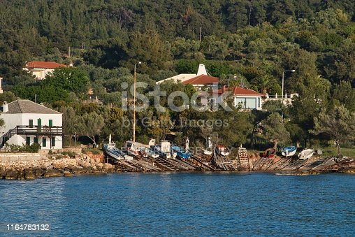 Thasos, Greece - April 29, 2019: Colorful boats on the shore and some houses among trees near the blue Aegean Sea in Thasos, Greece.