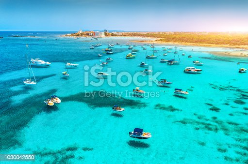 Boats and luxury yachts in transparent sea at sunset in summer in Mallorca, Spain. Aerial view. Colorful landscape with bay, azure water, sandy beach, blue sky. Balearic islands. Top view. Travel