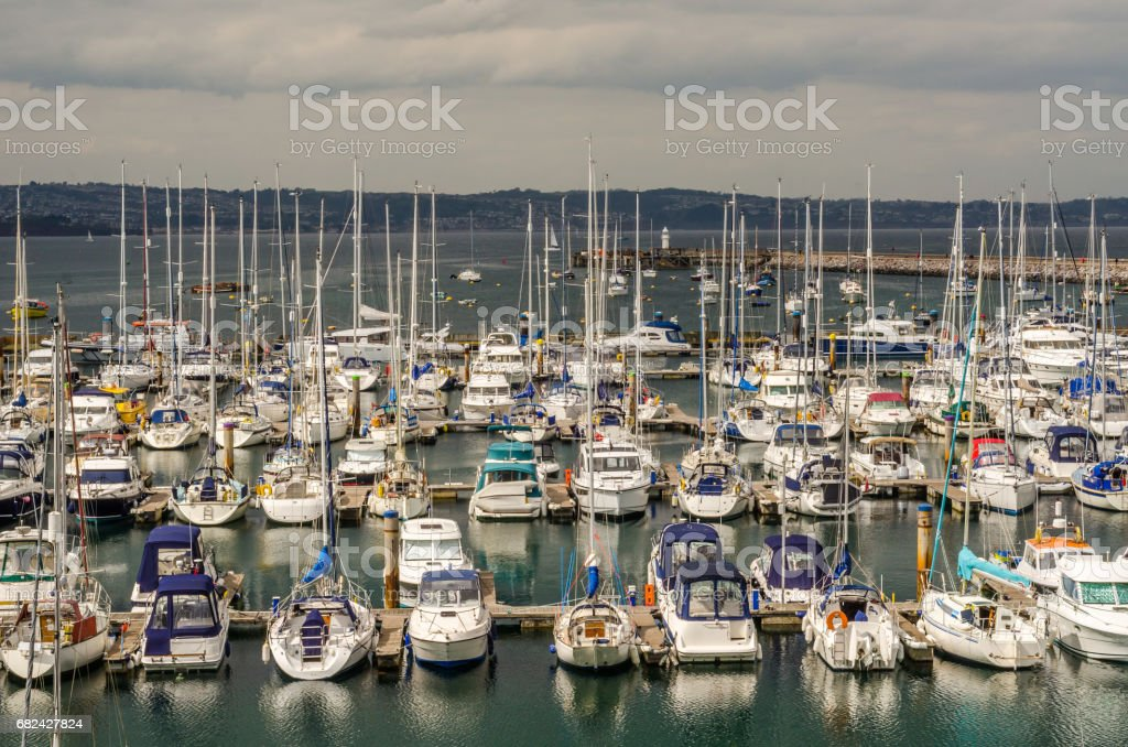 Boats and ships moored in a small port, in the background stone promenade and coastal town, fishing industry and tourism royalty-free stock photo
