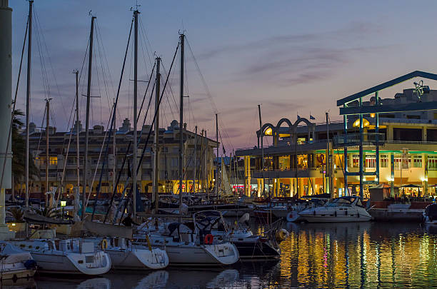 Boats at harbor in Puerto Marina at night stock photo