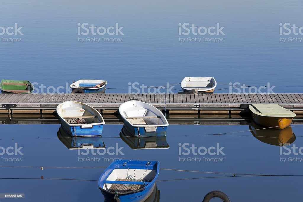 Boats at rest on a placid lake royalty-free stock photo