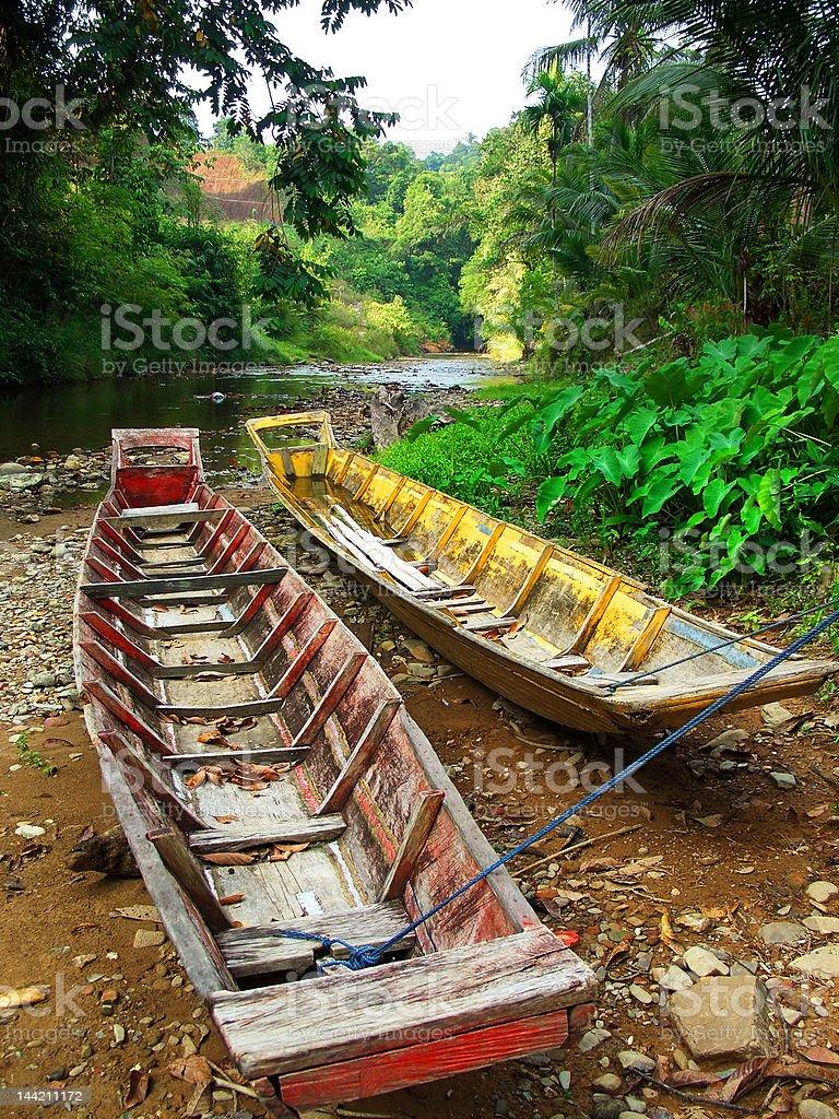 Boats beside a Borneo river in the jungle stock photo