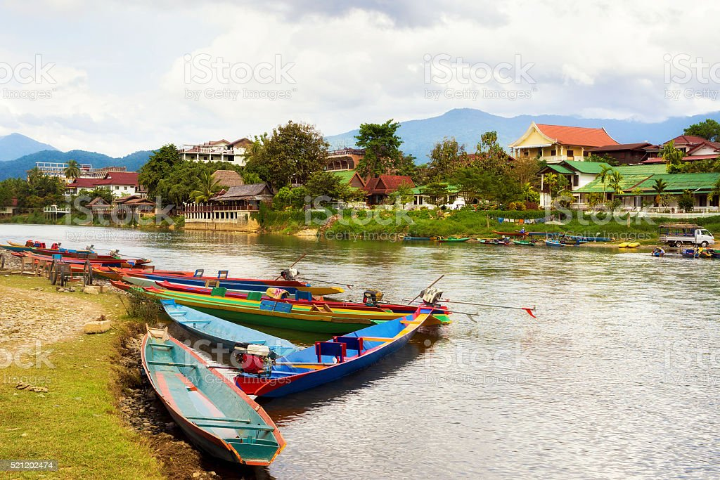 Boats by the Song River in Vang Vieng, Laos stock photo