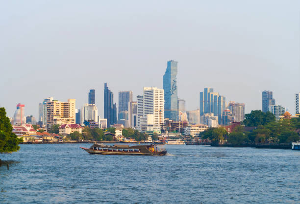 Boats cruise at Chao Phraya River with skyscraper buildings in Bangkok Downtown, urban city with blue sky, Thailand. Architecture landscape background. stock photo