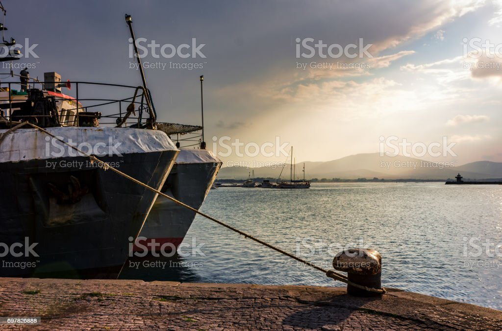 Boats docked to a mooring bollard in the  port of Sozopol at sunset stock photo