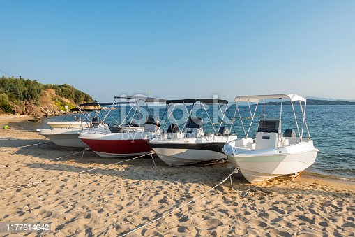 Boats for renting standing side by side on sand in Halkidiki, Greece