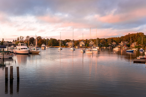 Boats in a beautiful Harbour surrounded by woods at sunset. Reflection in water.