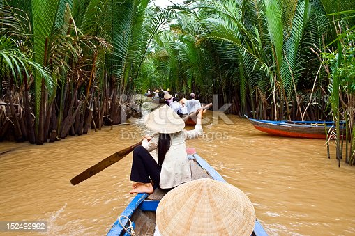 Vietnamese woman rowing a boat in Mekong River in Vietnam