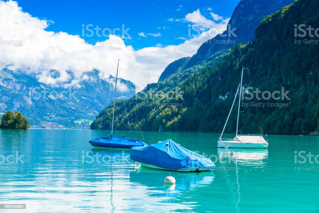 Boats in bay of Village Iseltwald at Lake Brienz - beautiful lake in the alps at Interlaken, Switzerland stock photo