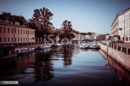 Boats In Fontanka River Canal And Apartment Buildings On Each Side In St. Petersburg, Russia