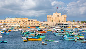 Alexandria, Egypt - November 15, 2018 :  \n\nThe citadel of Qaitbay stands on the site of the ancient lighthouse of Alexandria, one of the seven wonders of the ancient world. Medieval style, this citadel was built to protect the city but it now houses a museum where war remains are exhibited. This place, rich in history, is very popular with tourists and offers a breathtaking view of the Mediterranean and the corniche.\n\nwe see many boats of all sizes facing the citadel. The boats are both pleasure boats and fishing boats passing through or docked. There is really a lot of activity at this marina.\n\nStrategically positioned, 3 sides of the citadel are surrounded by the sea. Near the ramparts, there are a lot of pleasure boats which are are docked in this historic environment.