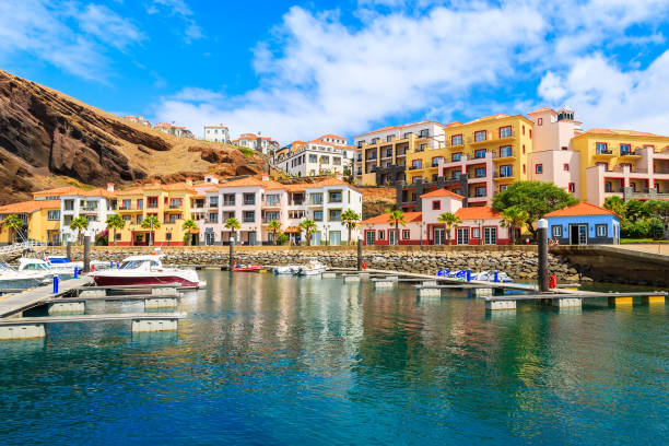 boats in marina with colourful houses near canical town on coast of madeira island, portugal - funchal imagens e fotografias de stock