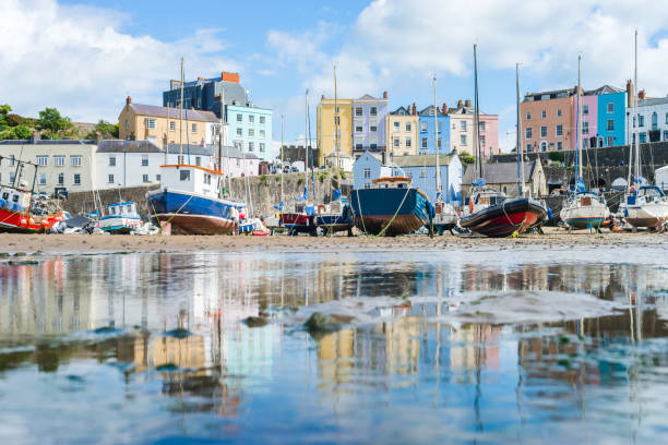 Boats in the bay at low tide with town view in Tenby bay, Wales Boats in the bay at low tide with town view in Tenby bay, Wales south wales stock pictures, royalty-free photos & images