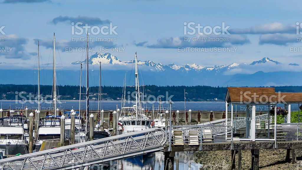 Boats in the Harbor Below Snow Capped Peaks stock photo