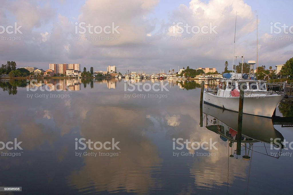 Boats in the Harbor with big clouds reflecting in the water stock photo