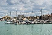 Heraklion, Crete, Greece - November 2, 2017: Old harbour of Heraklion with fishing boats and marina, Crete island, Greece.