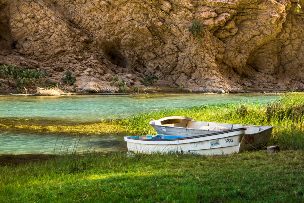 Boats in Wadi Shab in Oman Boats in Mountain river Wadi Shab in Oman with emerald green water riverbed stock pictures, royalty-free photos & images