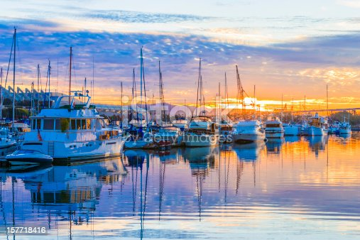 Dawn, sunrise. Pleasure boats, marina, sunrise clouds, colorful reflections in water. San Diego Harbor, California. Copy space in sky in upper quarter of photo. Also copy space in water in lower quarter of photo.