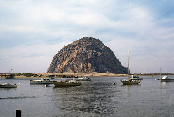 Boats moored in Morro Bay, circa 1974 A tranquil bay with several boats anchored in front of the majestic Morro Rock on the central California coast. hearkencreative stock pictures, royalty-free photos & images