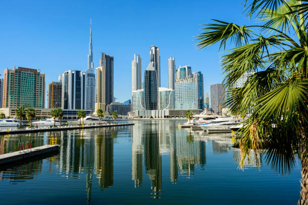 Boats Moored in the Marina and City Skyline in Dubai, United Arab Emirates. stock photo