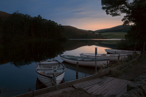 Boats moored to the shore of a night lake. Glencorse Reservoir in Pentland Regional Park. Scotland