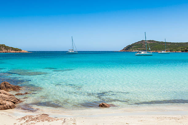 Boats mooring in the turquoise water of  Rondinara beach Corsica stock photo