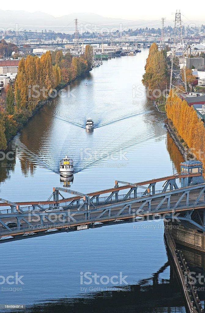 Boats motoring toward drawbridge on canal in Seattle stock photo