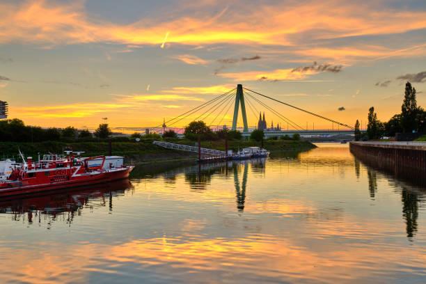 Boote der Wasserschutzpolizei und Feuerwehrboot in Köln-Deutz am Rhein bei Sonnenuntergang – Foto