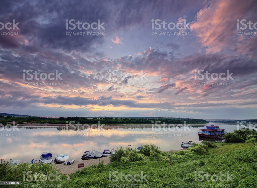 Boats on a riverside at sunrise. stock photo