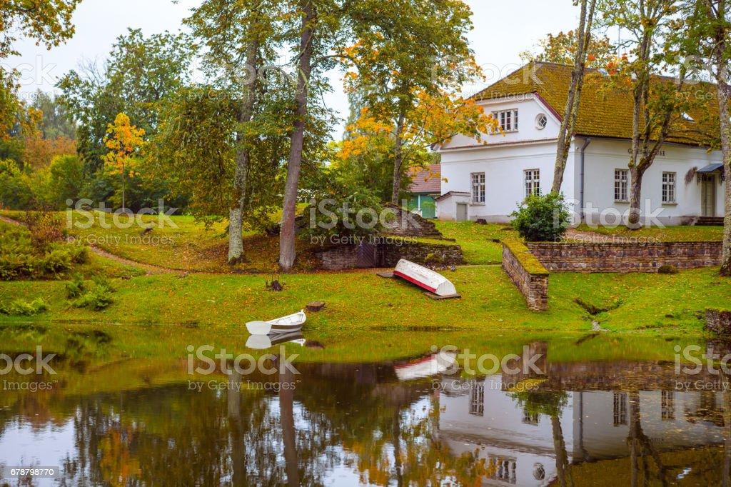 Tekneler kenarı gölet yakınındaki beyaz bir taş ev. Palmse manor, Estonya royalty-free stock photo