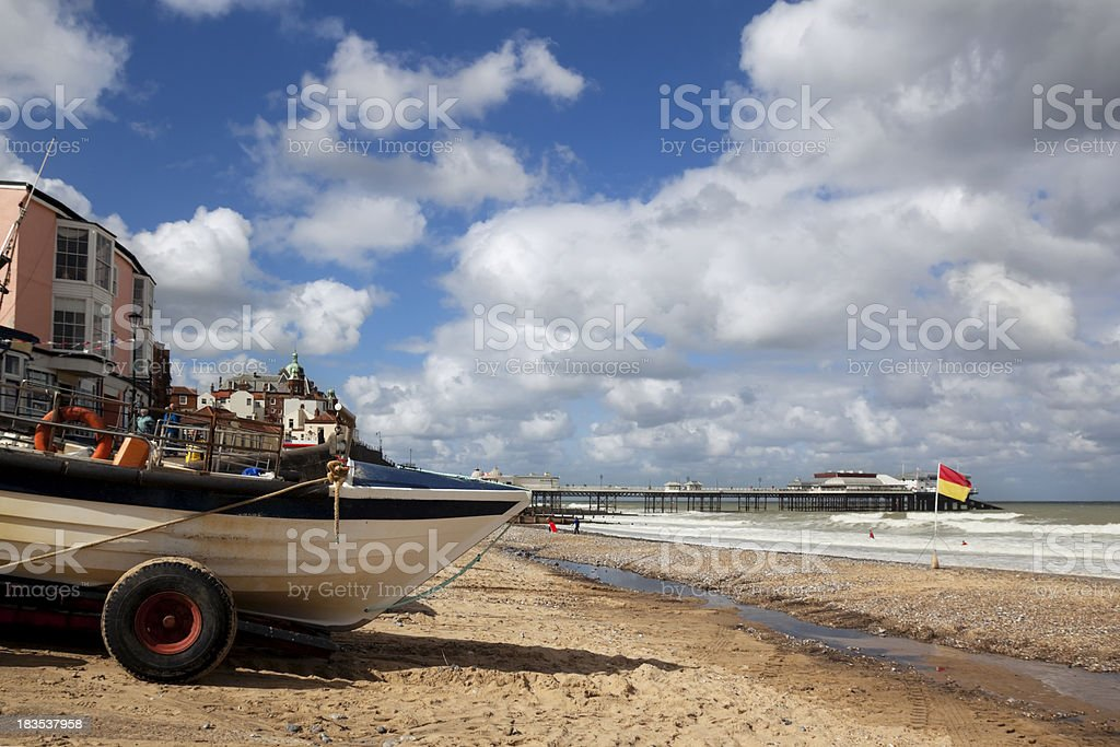 Boats on Cromer beach with a view of the pier stock photo