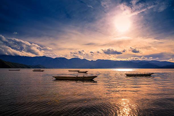 Boats on lake at sunset stock photo