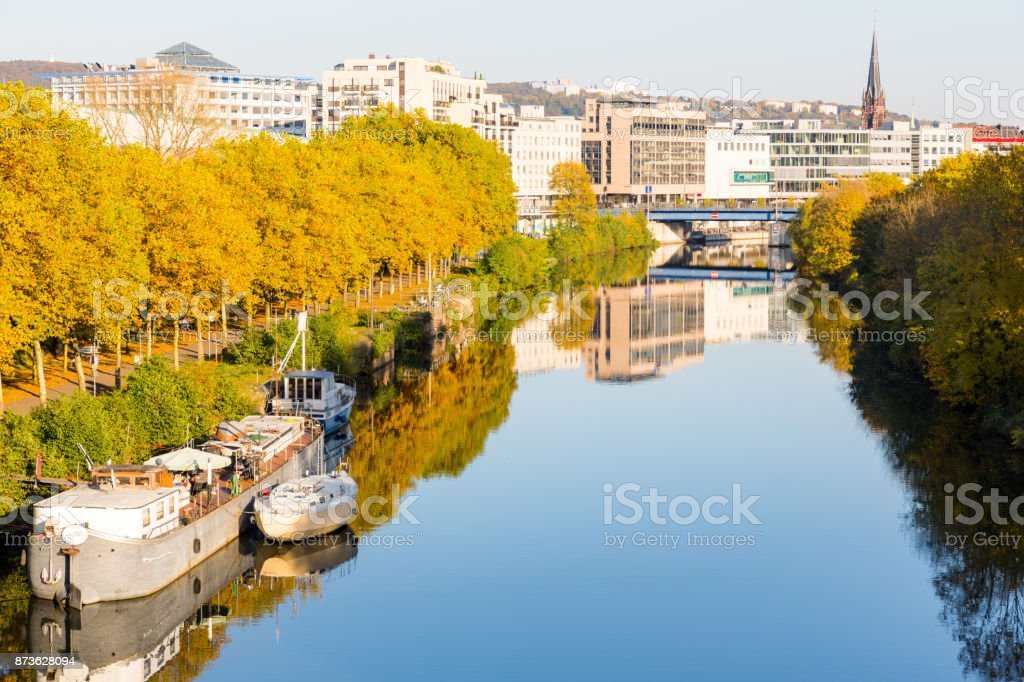 boats on river near promenade leading to city center with shopping malls and church stock photo