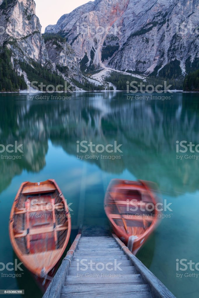 Boats on the Braies lake in the background of Seekofel mountain stock photo