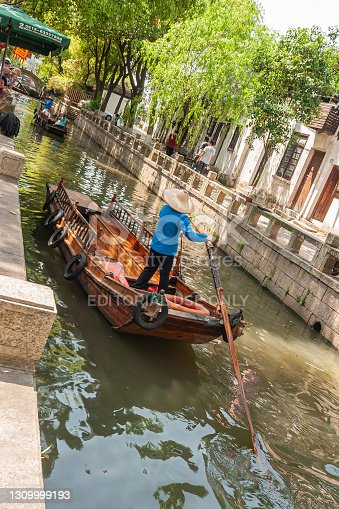 Tongli, China - May 2, 2010: Brown wooden boats on green water canal with housing on side and plenty of green foliage. Captain in blue up front.