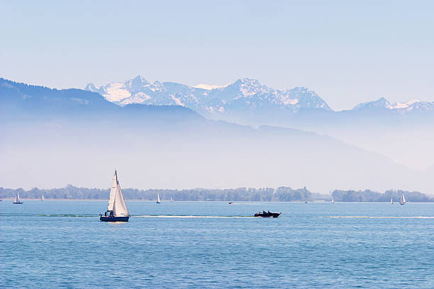 Boats on the Lake of Constance, snowy alps in the background Sail and motor boats on a quiet blue Lake of Constance with  Alps in the background. Snow on the peaks, ground fog in front of them. Bodensee stock pictures, royalty-free photos & images