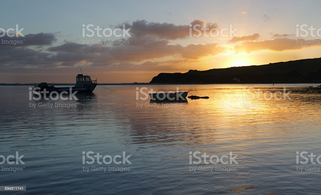 Boats on the water at sunrise stock photo