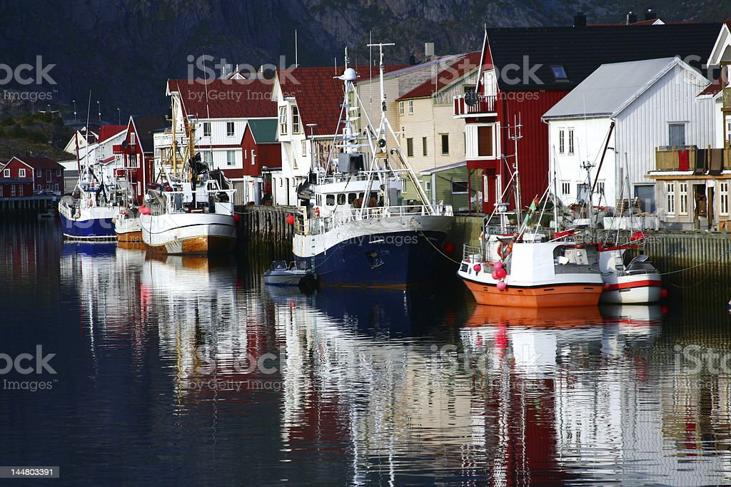 Boats reflecting in the water on the shore royalty-free stock photo
