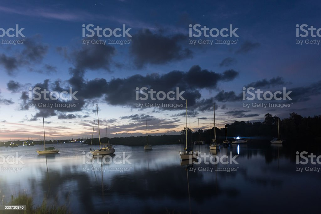 Boats sitting in the lake at sunset in Yamba, Australia stock photo